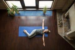 Yoga à la maison : Pose de torsion de ventre photo libre de droits