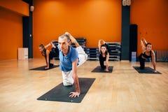 Yoga étirant la formation, groupe avec l'instructeur Photos libres de droits