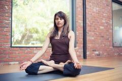 Yoga-Üben: Junge Frau, die im Lotussitz in a sitzt stockbild