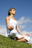 Yoga. Pretty woman in white doing yoga outdoor Stock Photography