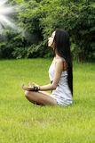 Yoga. Asian girl is doing yoga on the grass Royalty Free Stock Photos