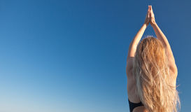 Yoga. Young woman making yoga postures, under a deep blue sky Royalty Free Stock Photo