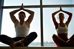 Yoga. Photo of meditating people sitting with their arms raised and kept in touch Royalty Free Stock Images