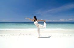 Yoga. Woman practising Yoga (Warrior Position) on the beach Royalty Free Stock Photos