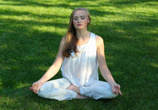 Yoga. Beautiful young woman meditating in a lawn Royalty Free Stock Photos