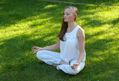Yoga. Beautiful young woman meditating in a garden Stock Images