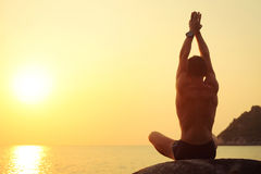 Yoga. Young man stretching on a rock at sunset light Royalty Free Stock Photography