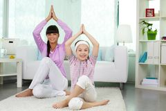Yoga. Portrait of little girl and her mother doing yoga exercise at home Royalty Free Stock Image