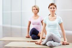 Yoga. Young girls do yoga indoors Royalty Free Stock Photos
