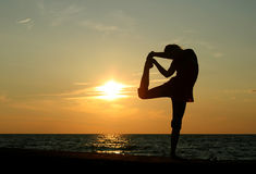 Yoga. Silhoette of teenager doing yoga at sunset Royalty Free Stock Image