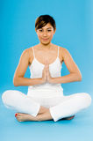 Yoga. A young Asian woman in white practising yoga in studio on blue background Stock Photo