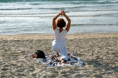 Yoga. Young lady ,practicing yoga on the beach stock photo