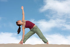 Yoga. A woman strikes a yoga pose on a sand dune in California Royalty Free Stock Image