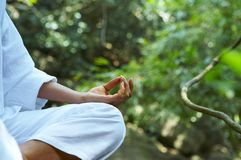 Yoga. Fragment like image of young woman practicing yoga in tropic environment Royalty Free Stock Photo