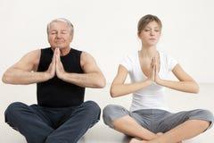 Yoga. Senior man and young woman doing yoga Royalty Free Stock Photography
