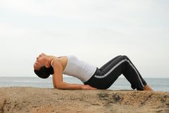 Yoga. Young Woman Exercising Yoga in the rocky beach Royalty Free Stock Photo
