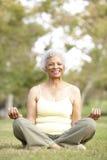 Yoga aîné de femme en stationnement Photographie stock libre de droits