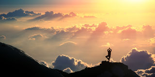 Yoga above the clouds. Practicing yoga outdoors. A person is standing in Vriksasana (Tree pose Royalty Free Stock Image