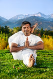 Yoga Advance pose in mountains. Yoga meditation eka pada shirshasana foot behind the head pose by concentrate Indian Man in white cloth in the morning at Royalty Free Stock Photography
