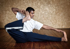 Yoga akarna dhanurasana archer pose. Handsome Indian man in white shirt doing akarna dhanurasana, archer pose indoors on wooden floor at grunge background royalty free stock photos