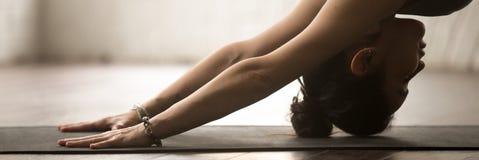 Yoga allegra di pratica della donna della foto orizzontale che fa cane orientato verso il basso fotografie stock libere da diritti