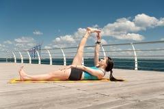 yoga Anantasana di posa contro il mare immagine stock