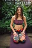 Yoga andante della giovane donna caucasica su una stuoia alla serra Fotografie Stock Libere da Diritti