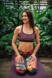 Yoga andante della giovane donna caucasica su una stuoia alla serra Immagine Stock Libera da Diritti