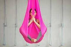 Yoga antigravedad aérea de la actitud del loto de la muchacha La mujer se sienta en hamaca Imagen de archivo