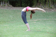 Yoga Ardha Chandrasana (back bend) pose by woman on lawn Stock Photography