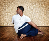 Yoga ardha matsiendrasana twist pose. Handsome Indian man in white shirt doing ardha matsiendrasana twist pose indoors on wooden floor at grunge background royalty free stock images