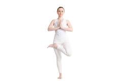 Yoga Ardha Padma Vrikshasana pose. Sporty attractive young woman in white sportswear doing exercise for spine, Ardha Padma Vrikshasana, hands in Namaste, leg in Stock Photography