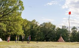 Yoga at Art-Labyrinth Summer. Group of people doing yoga in park at sunset, park in countryside with canadian tent and red flag hoisted on a very tall wooden rod stock photos