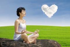 Yoga asiatica di esercizio della donna sotto la nuvola di amore Immagine Stock