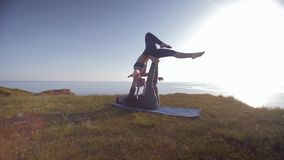 Yoga, athletic female acrobat is balancing on legs and hands of her male partner in sunlight on background of sky and. Yoga, athletic female acrobat is balancing stock footage