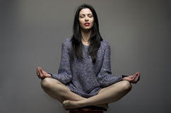 Yoga. Attractive girl, woman with long black hair sitting on sto Stock Photos