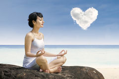 Yoga attraente di esercizio della donna sotto la nuvola di amore alla spiaggia Immagini Stock Libere da Diritti