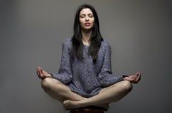 yoga Attraktives Mädchen, Frau mit dem langen schwarzen Haar, das auf sto sitzt Stockfotos