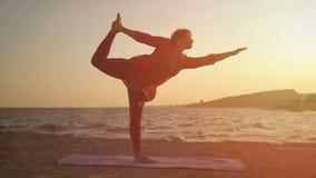 Yoga au coucher du soleil sur la plage femme faisant le yoga, exécutant des asanas banque de vidéos