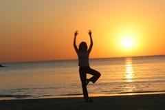 Yoga auf Aviv-Strand am Sonnenuntergang Stockfotos