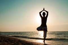 Yoga auf dem Strand bei Sonnenaufgang. Stockfoto