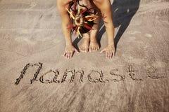 Yoga auf dem Strand mit Namaste Stockfotos