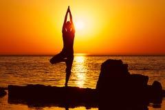 Yoga auf Sonnenuntergang Stockbild