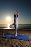 Yoga auf Strand mit Sonnenaufgang Stockbilder
