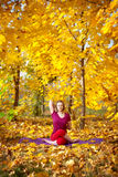 Yoga in autumn. Yoga gomukhasana cow pose by concentrate beautiful woman in red cloth and yellow leaves around in the autumn Royalty Free Stock Photography