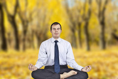 Yoga in autumn park. Business man meditating in work shirt and tie Stock Photo