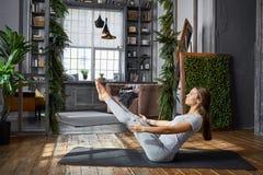 Yoga avancé de pratique de femme dans le salon à la maison Une série de poses de yoga Photo libre de droits