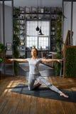 Yoga avancé de pratique de femme dans le salon à la maison Une série de poses de yoga Images libres de droits