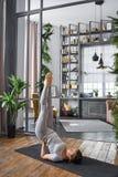Yoga avancé de pratique de femme dans le salon à la maison Une série de poses de yoga Photos libres de droits