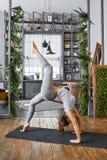 Yoga avancé de pratique de femme dans le salon à la maison Une série de poses de yoga Image libre de droits